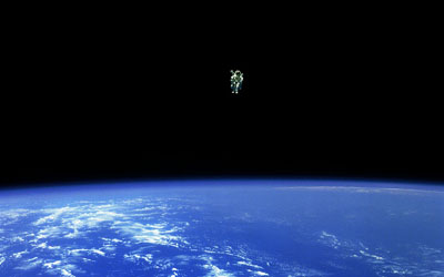 "Mission Specialist Bruce McCandless II, is seen further away from the confines and safety of his ship than any previous astronaut has ever been. This space first was made possible by the Manned Manuevering Unit or MMU, a nitrogen jet propelled backpack. After a series of test maneuvers inside and above Challenger's payload bay, McCandless went ""free-flying"" to a distance of 320 feet away from the Orbiter. This stunning orbital panorama view shows McCandless out there amongst the black and blue of Earth and space. Credit: NASA"